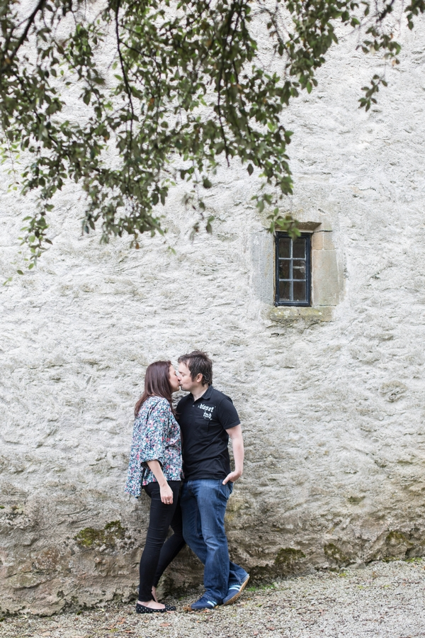 Engaged couple kissing by Sizergh Castle
