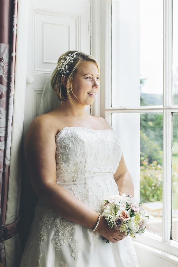 Bride standing by window