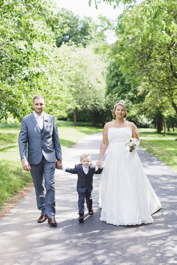 Bride and groom walking with son