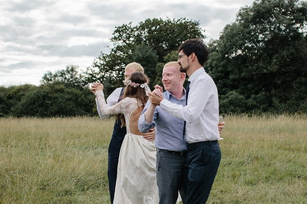 Wedding guests dancing in field