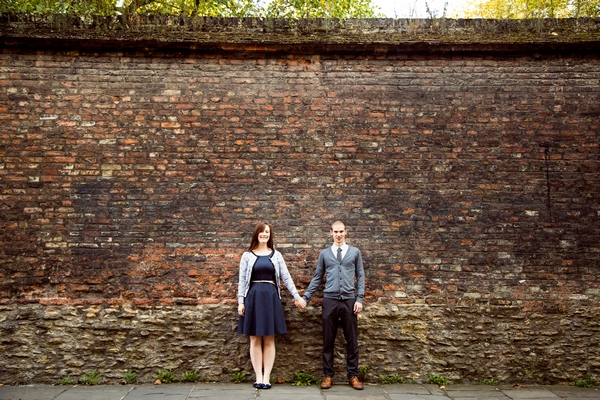Couple holding hands in front of wall