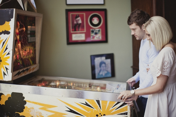Engaged couple playing pinball