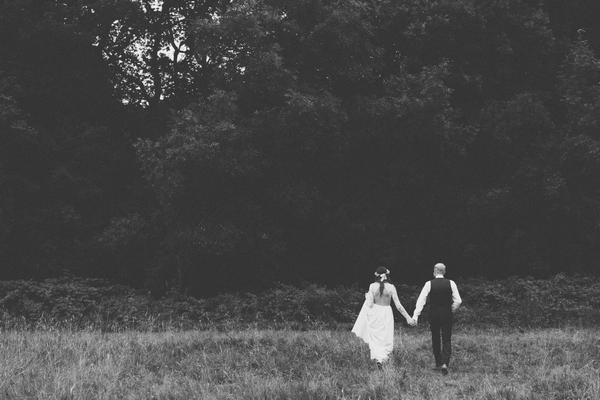Bride and groom walking to woods