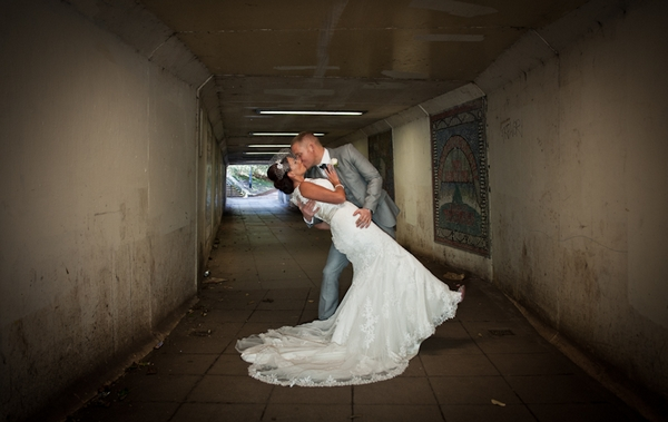 Bride and groom kissing in subway