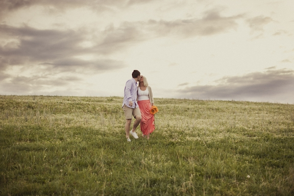 Engaged couple walking across field