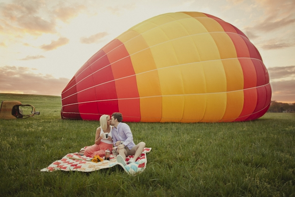 Engaged couple sitting in front of hot air balloon