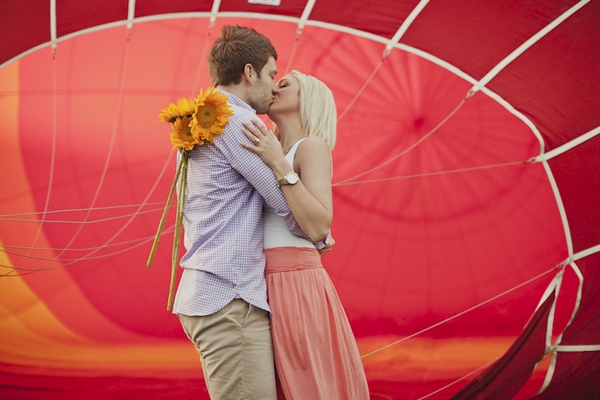 Engaged couple kissing in front of hot air balloon