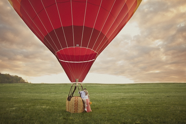 Engaged couple on edge of hot air balloon basket