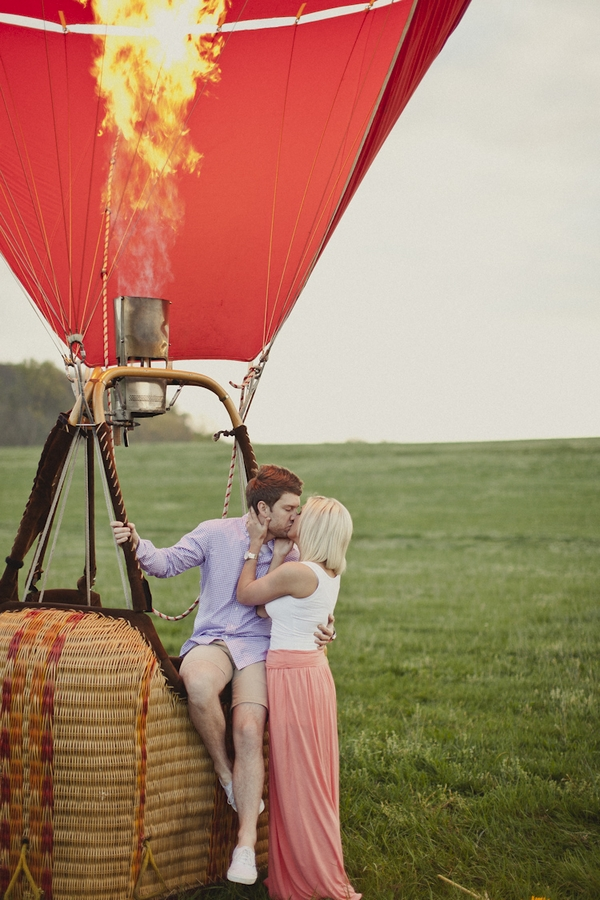 Engaged couple kissing on edge of hot air balloon basket