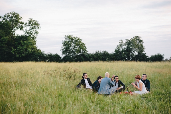 Wedding guests sitting in field