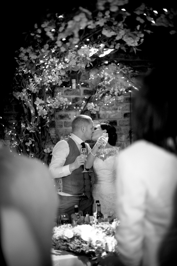 Bride and groom kissing during toast