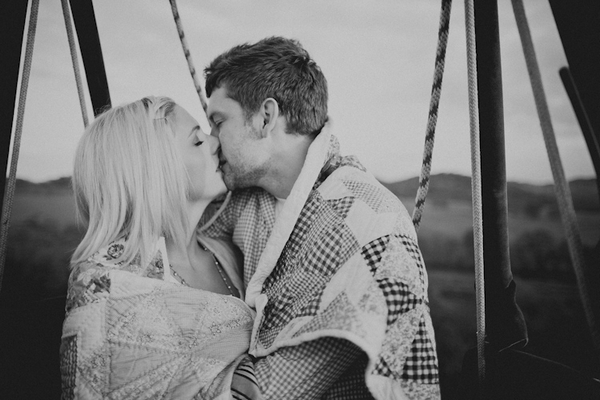 Engaged couple kissing in hot air balloon