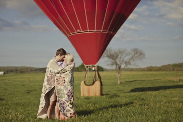 Engaged couple in front of hot air balloon