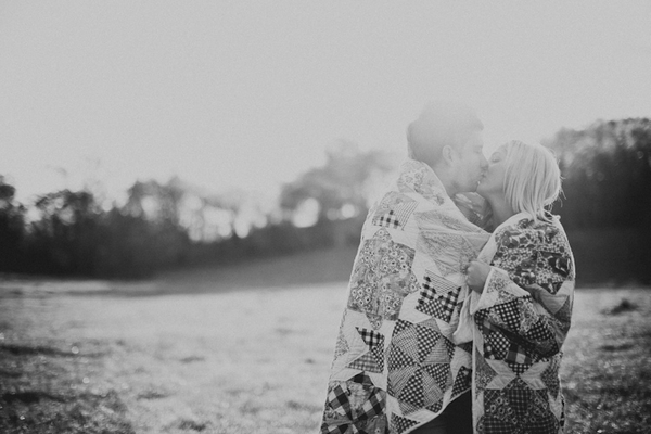 Engaged couple wrapped in blanket