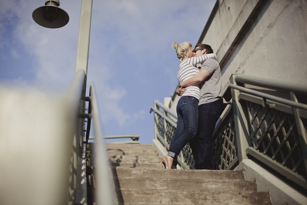 Engaged couple kissing on steps