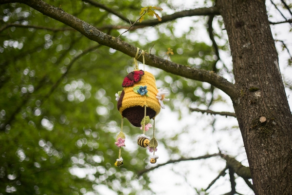 Knitted beehive hanging from tree
