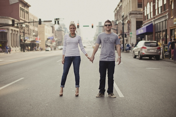 Engaged couple holding hands in road