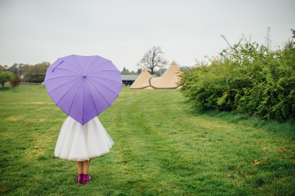 Bride holding purple heart umbrella