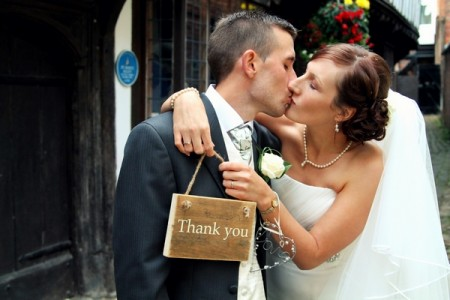 Bride and groom kissing with haolding thank you sign - Picture by Twirly Girl Photography