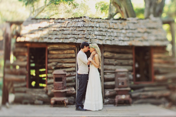 Man and woman outside log cabin