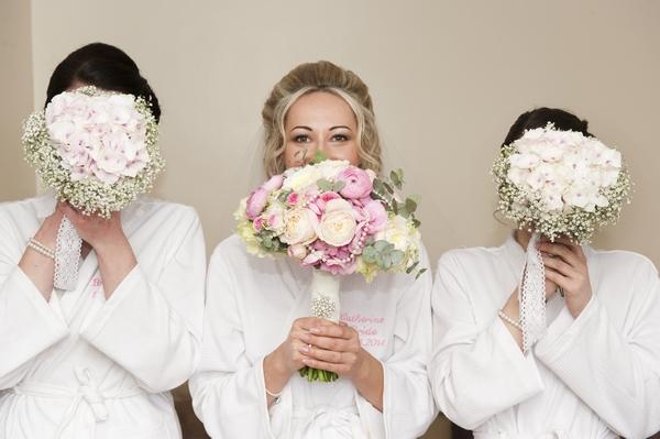 Bride and bridesmaids hiding behind bouquets