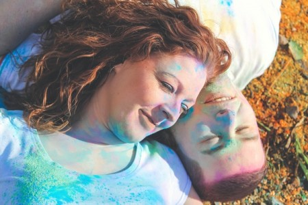 Couple laying down covered in holi powder