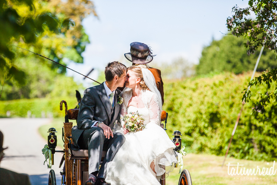 Bride and groom kissing on horse and cart