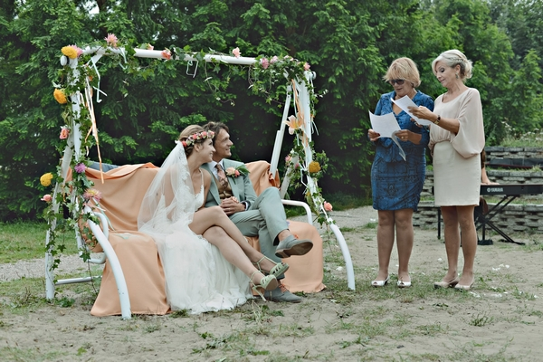 Bride and groom sitting on rocking bench during reading