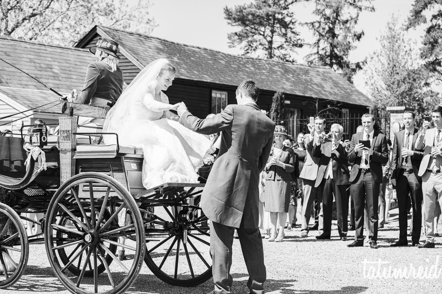 Groom helping bride off of horse and cart