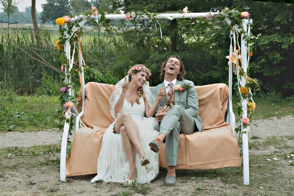 Bride and groom sitting on rocking bench