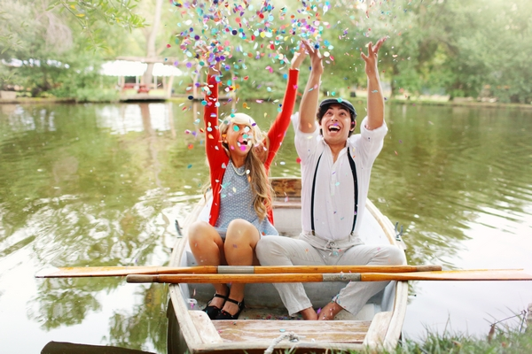 Couple on rowing boat throwing confetti