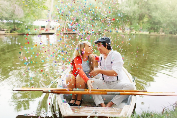 Couple on rowing boat with confetti coming down