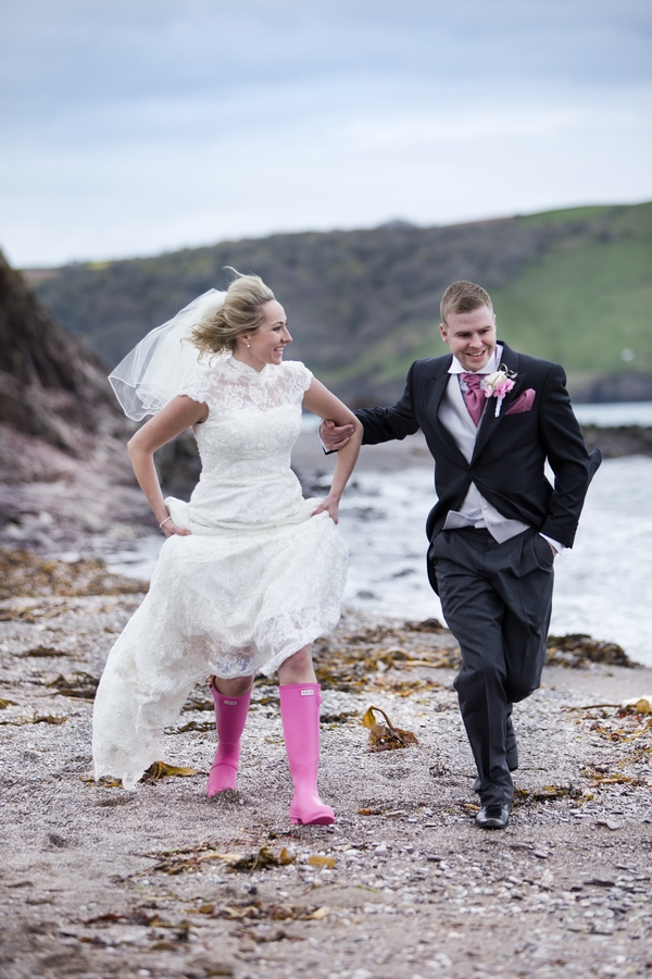 Bride in wellies and groom running on beach
