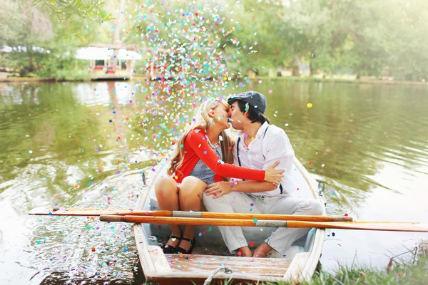 Couple kissing on rowing boat with confetti
