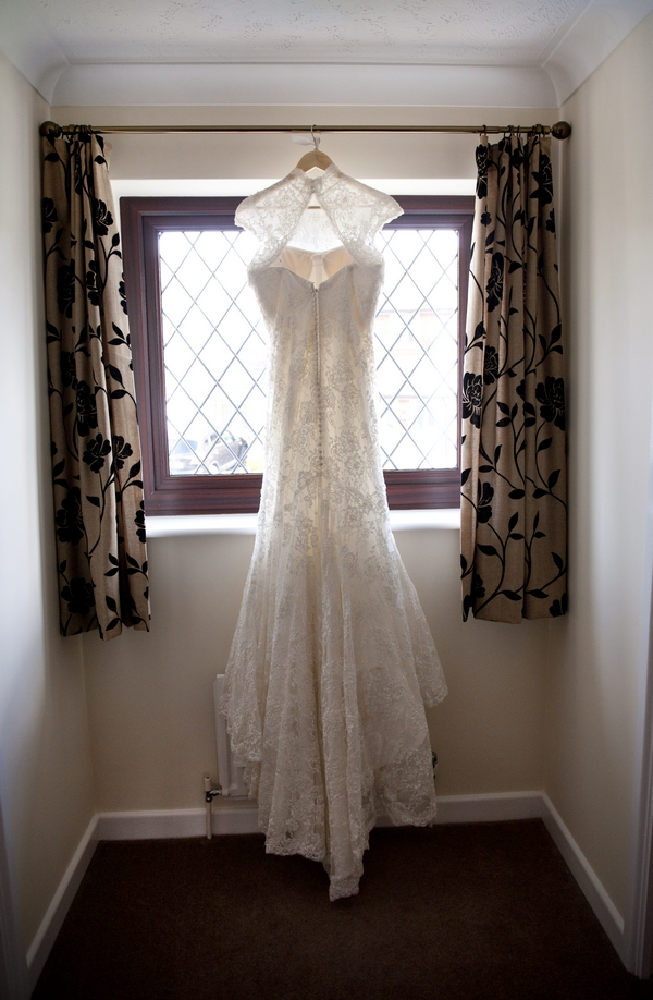 Lace wedding dress hanging in window