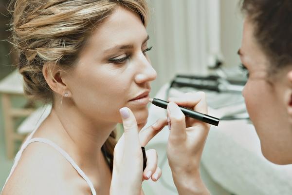 Bride having lip liner applied