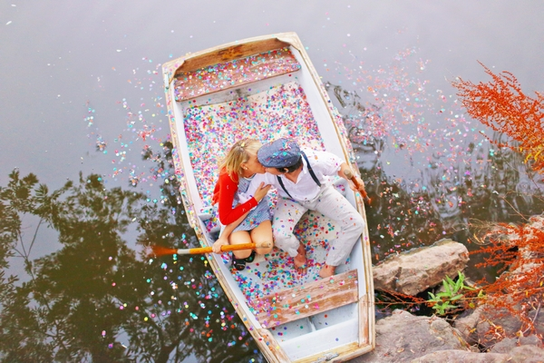 Couple on rowing boat covered in confetti