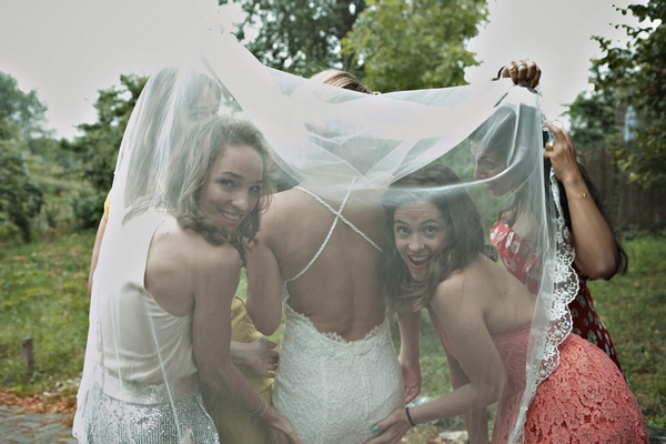 Bride and bridesmaids under veil