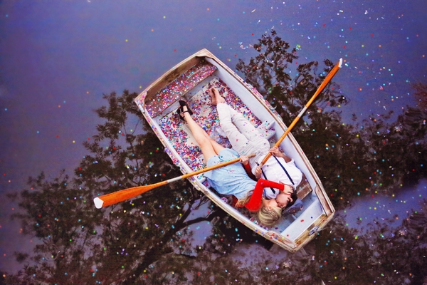 Couple laying on rowing boat covered in confetti
