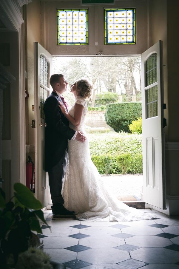 Bride and groom leaning against door