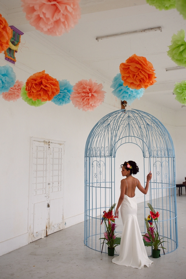 Bride standing next to large bird cage