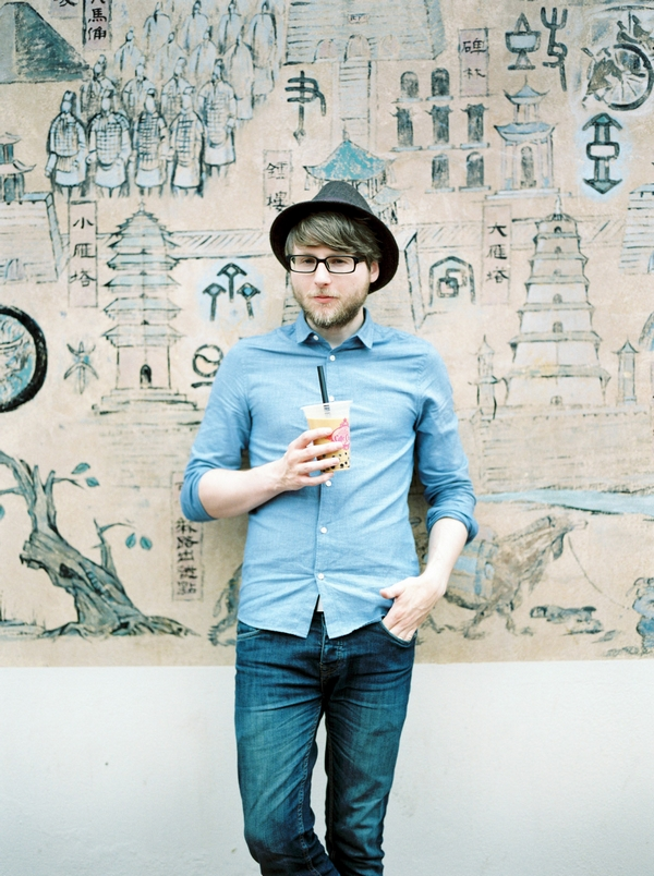 Man standing against picture wall