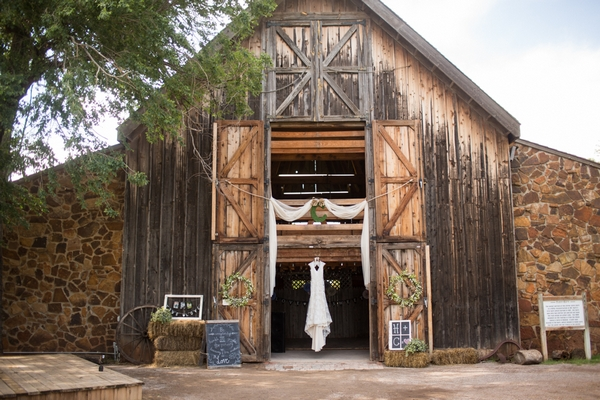 Wedding dress hanging in entrance to barn