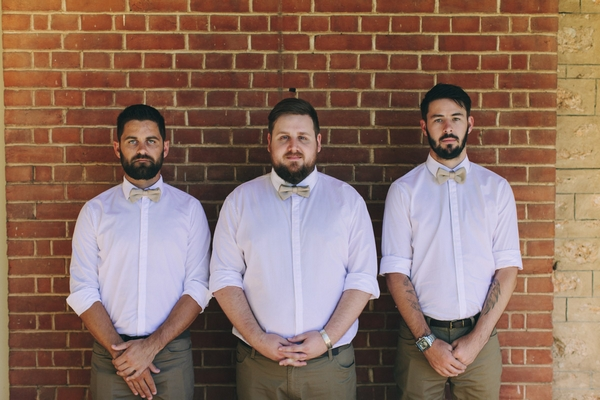 Groomsmen standing against wall