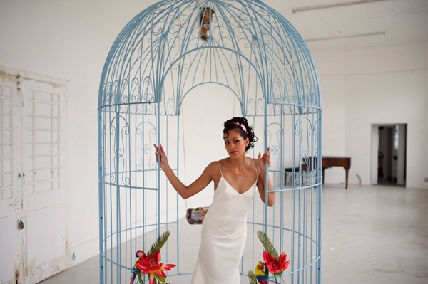 Bride standing in large bird cage