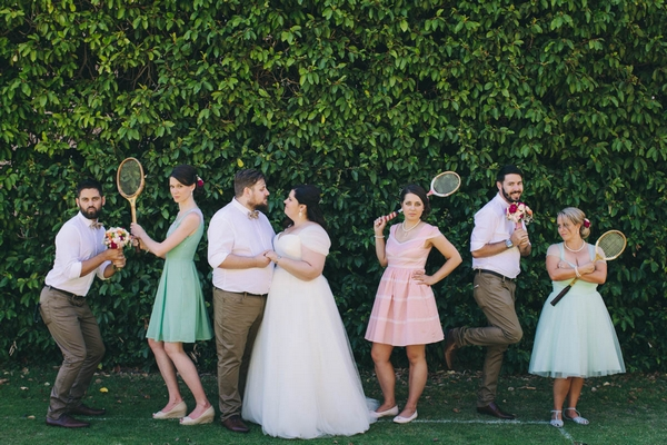 Bride, groom and bridal party holding tennis rackets