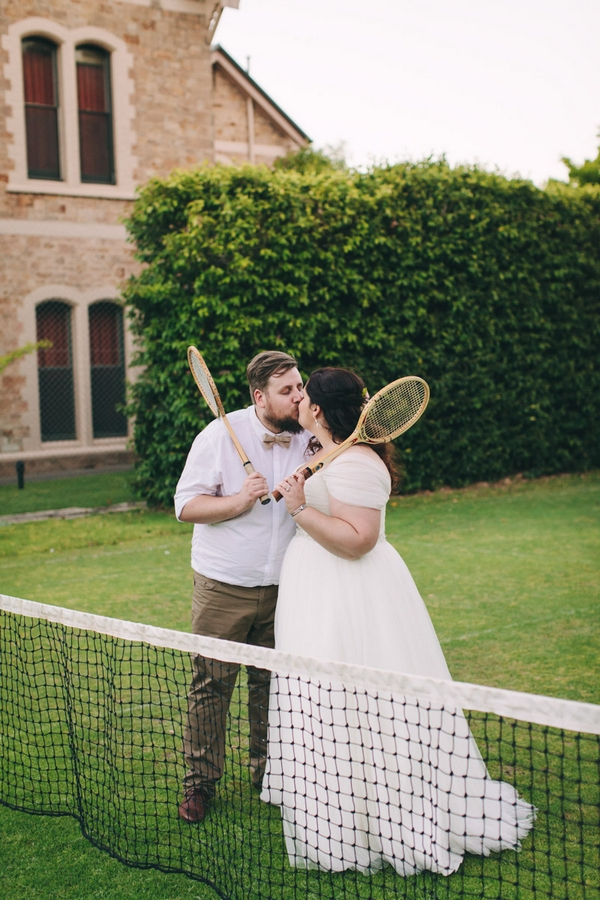 Bride and groom kissing holding tennis rackets