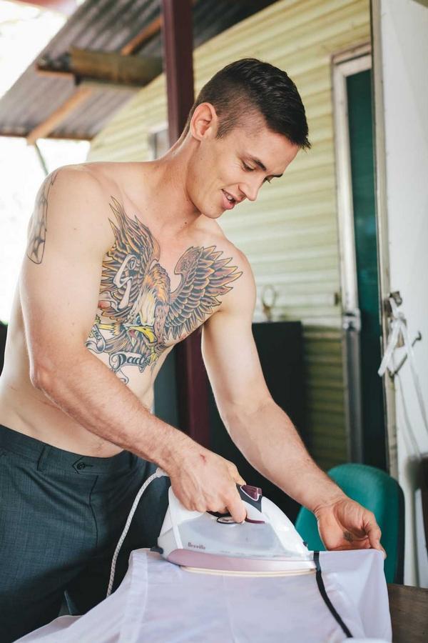 Man with large tattoo ironing
