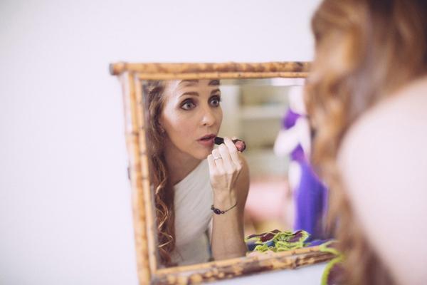 Bride putting on lipstick in mirror