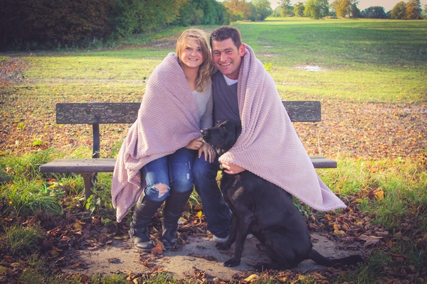 Couple sitting on bench wrapped in blanket